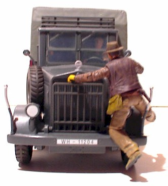 Indiana Jones hangs onto the desert convoy truck